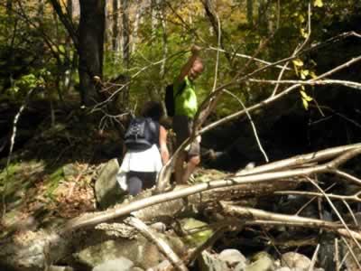 hikers crossing brook
